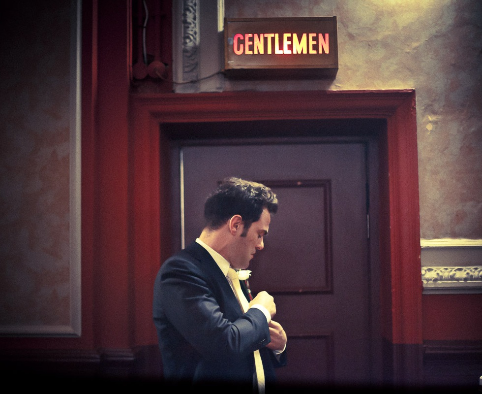 wedding photograph best man in front of gentlemen sign at gate cinema in notting hill